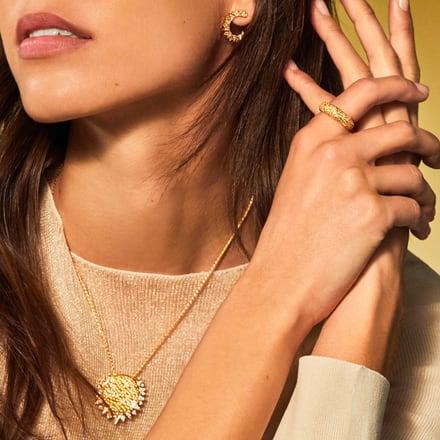 一位女士佩戴黃金鉆石墜飾和高級耳環